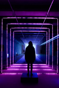 Neon colored picture of a dark hooded figure facing into the opening of a labyrinth